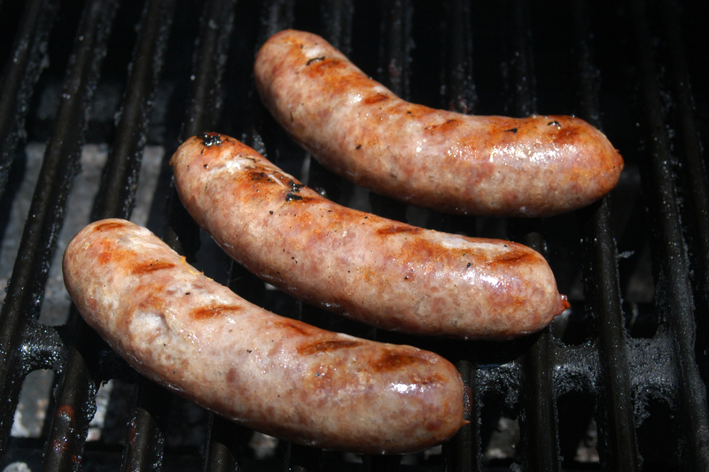Image of three Fareway bacon cheddar bratwursts on a grill.