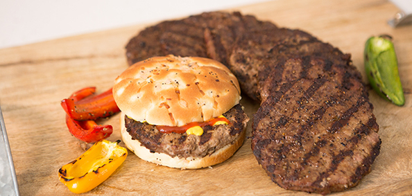 Image of premium steak burger patties and one finished burger.