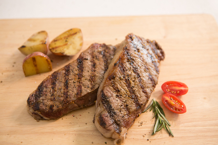 Image of two cooked New York Strip Steaks.