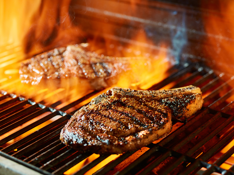Image of steaks being cooked on the grill.