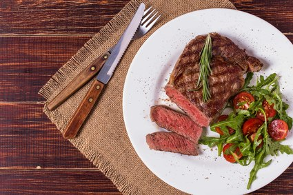 Image of a ribeye steak on plate, part of the Heartland Package.
